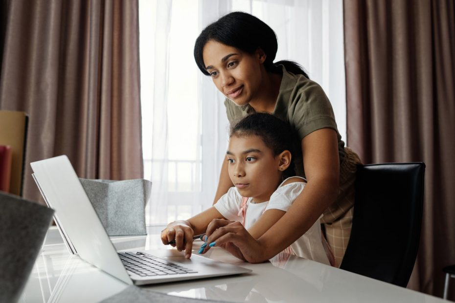 A mom helping her young son with homework on a laptop